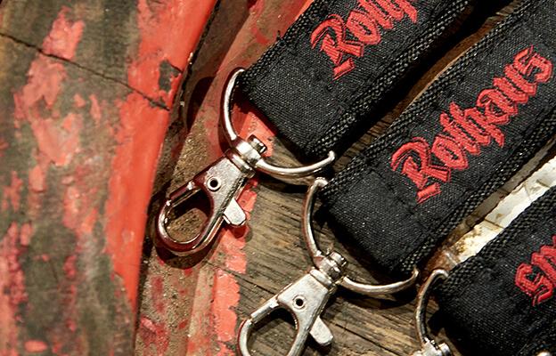 Drei edle, graue Kleiderbügel hängen an einer Stange mit dem Aufdruck des Rothaus Schriftzug.